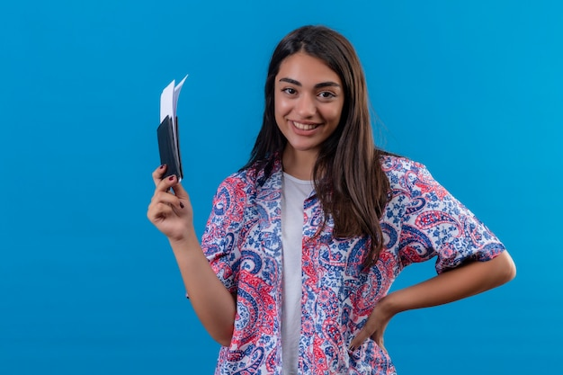 Jonge mooie vrouw toeristische bedrijf paspoort met kaartjes kijken camera glimlachend vrolijk positief en gelukkig klaar voor vakantie staande over geïsoleerde blauwe achtergrond Gratis Foto