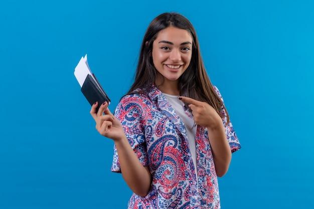 Jonge mooie vrouw toeristische bedrijf paspoort met kaartjes kijken camera wijzend met wijsvinger naar hen glimlachend vrolijk staande over geïsoleerde blauwe achtergrond Gratis Foto