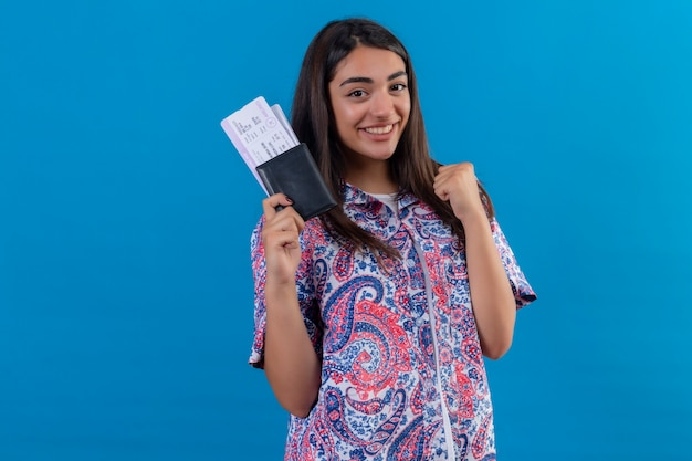 Jonge mooie vrouw toeristische bedrijf paspoort met kaartjes kijken opgewonden verheugend haar succes en overwinning haar vuist balancerend met vreugde blij haar doel en doelen te bereiken staande over isolaat Gratis Foto