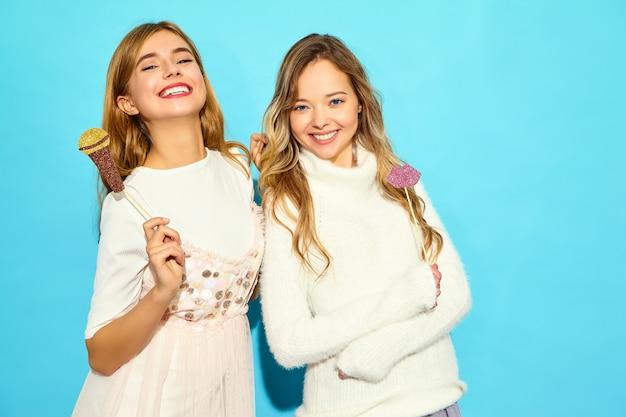 Jonge mooie vrouw twee zingen met rekwisieten nep microfoon. trendy vrouwen in casual zomer kleding. grappige modellen die op blauwe muur worden geïsoleerd Gratis Foto