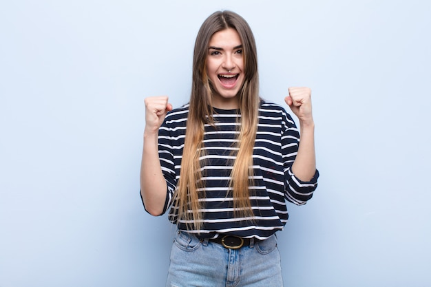 Jonge mooie vrouw voelt zich geschokt, opgewonden en gelukkig, lacht en viert succes en zegt wow! tegen zachte blauwe muur Premium Foto