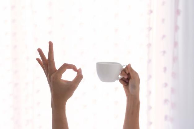 Jonge mooie vrouw wakker in de ochtend in het bed, strekt zijn armen met een kopje koffie en toont ok teken. Premium Foto