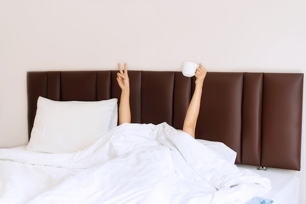 Jonge mooie vrouw wakker in de ochtend in het bed Premium Foto