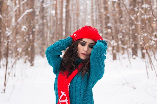 Jonge mooie vrouw wandelen in het winter besneeuwde park op zonnige dag Premium Foto