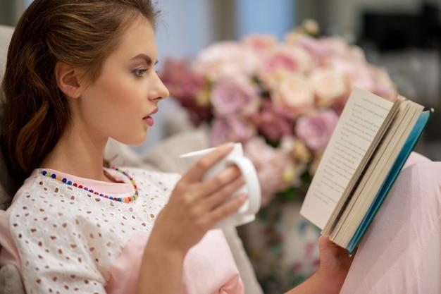 Jonge mooie vrouw zittend op de bank koffie drinken en lezen van een boek geniet van rust Gratis Foto