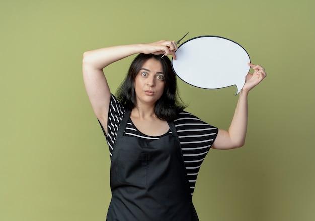 Jonge mooie vrouwelijke kapper die in schort het lege teken van de toespraakbel boven het hoofd houdt verward status over lichte muur Gratis Foto