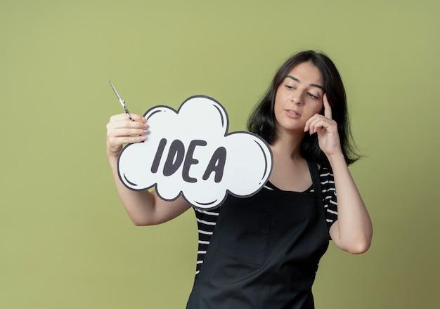 Jonge mooie vrouwelijke kapper in schort met schaar en lege tekstballon bord met idee woord kijken verbaasd staande over lichte muur Gratis Foto
