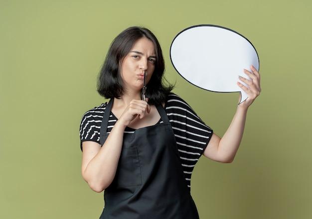 Jonge mooie vrouwelijke kapper in schort met schaar leeg tekstballon bord met zelfverzekerde uitdrukking staande over lichte muur Gratis Foto