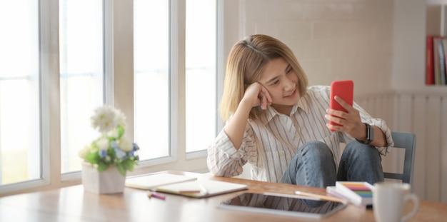 Jonge mooie vrouwelijke ontwerper die smartphone bekijkt en op de stoel zit Premium Foto