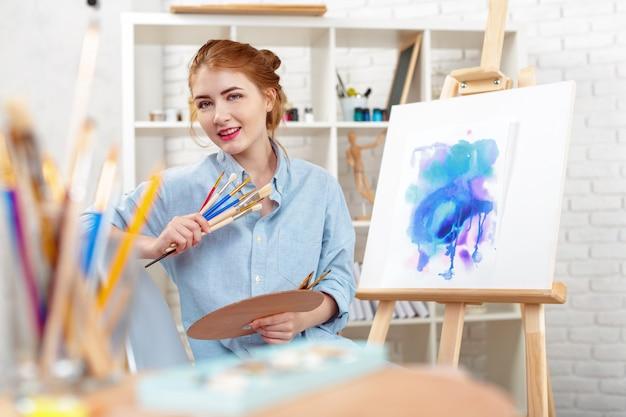 Jonge mooie vrouwenkunstenaar die het abstracte schilderen op een schildersezel trekt Premium Foto