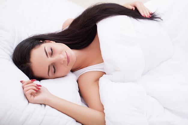 Jonge mooie vrouwenslaap in de slaapkamer. detailopname. Premium Foto