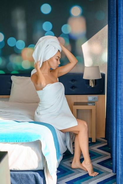 Jonge mooie vrouwenzitting op bed in handdoek, conceptenochtend. Premium Foto