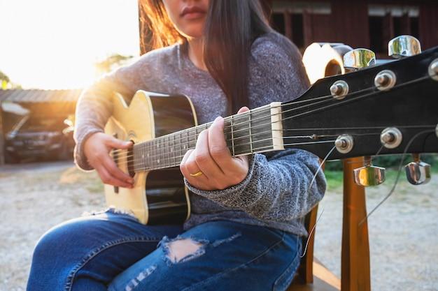 Jonge mooie vrouwenzitting op stoel die een lied samenstelt Premium Foto