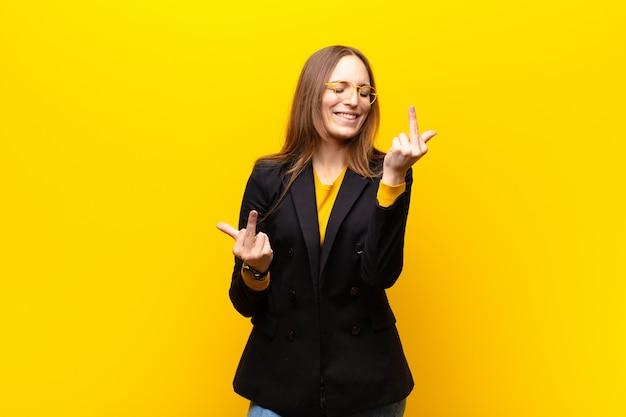 Jonge mooie zakenvrouw voelt provocerend, agressief en obsceen, flipping de middelvinger, met een opstandige houding tegen oranje muur Premium Foto
