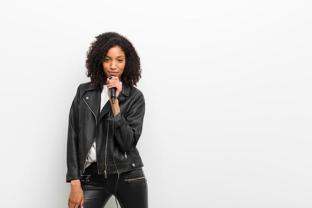 Jonge mooie zwarte vrouw met een microfoon die een leerjasje op witte muur draagt Premium Foto