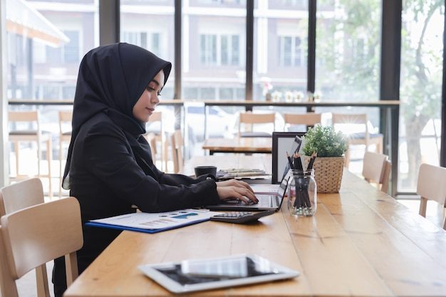 Jonge moslimonderneemster die op het kantoor werkt Premium Foto