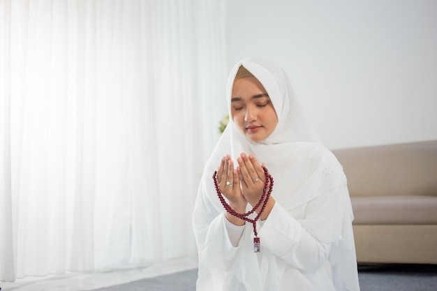 Jonge moslimvrouw bidden in witte traditionele kleding Premium Foto