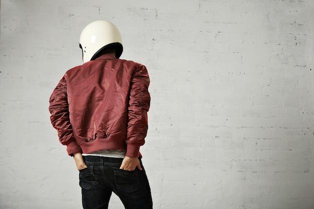Jonge motorrijder in witte helm en rode nylon jas schot vanaf de achterkant met zijn handen in de achterzakken van zijn spijkerbroek in een studio met witte muren. Gratis Foto