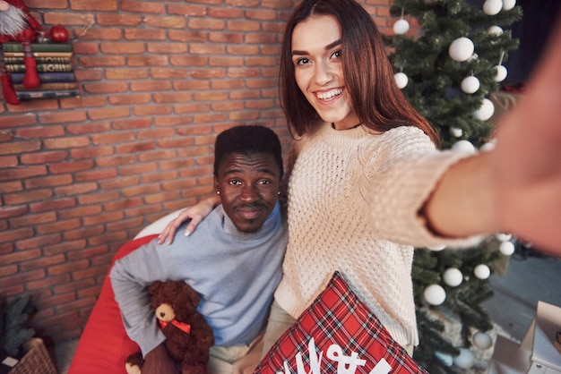 Jonge multi-etnische kerstmis die van de paarvergadering huis koesteren. nieuwjaar. feestelijke stemming van een man en een vrouw Premium Foto