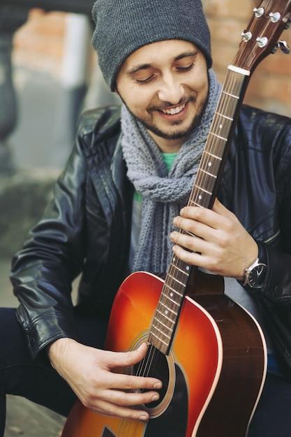 Jonge muzikant met gitaar in stad Gratis Foto