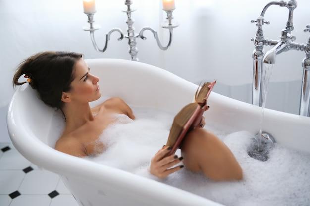Jonge naakte vrouw die een ontspannend schuimend bad neemt en een boek leest Gratis Foto