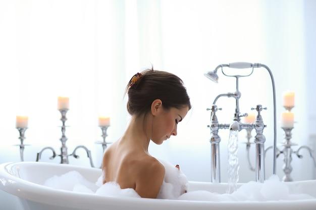 Jonge naakte vrouw die een ontspannend schuimend bad neemt Gratis Foto