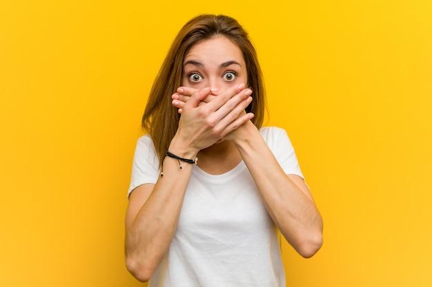 Jonge natuurlijke kaukasische geschokte vrouw behandelend mond met handen. Premium Foto