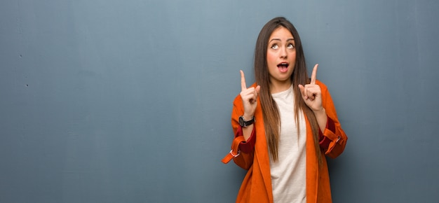 Jonge natuurlijke vrouw verrast omhoog iets te tonen Premium Foto