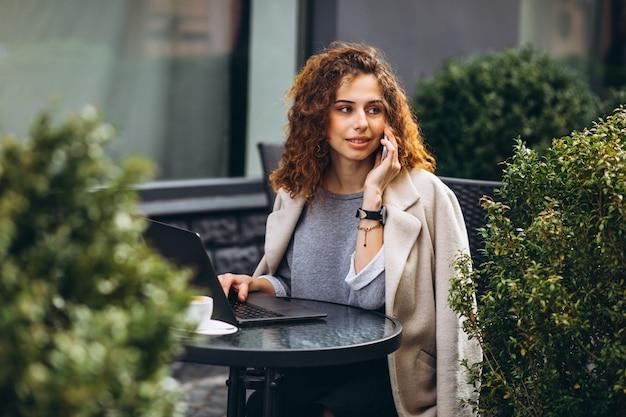 Jonge onderneemster die aan een computer buiten het koffie werkt Gratis Foto