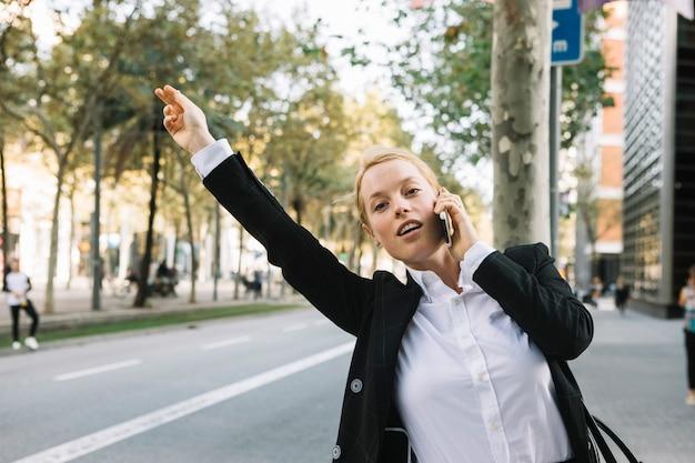 Jonge onderneemster die hand opheft voor het tegenhouden van auto op stadsweg Gratis Foto