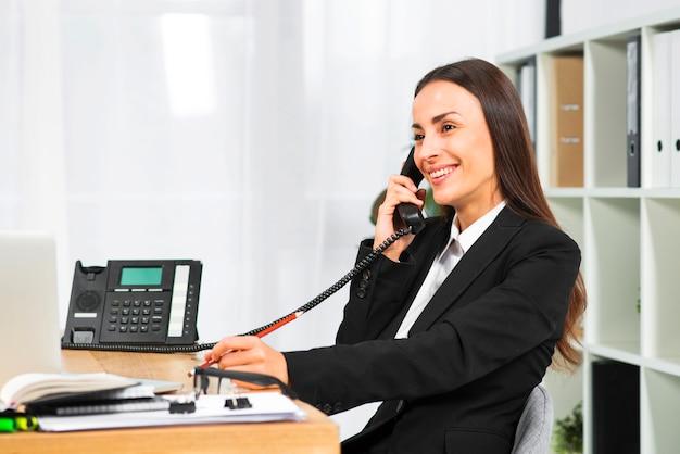 Jonge onderneemster die terwijl het spreken op telefoon in het bureau glimlacht Gratis Foto