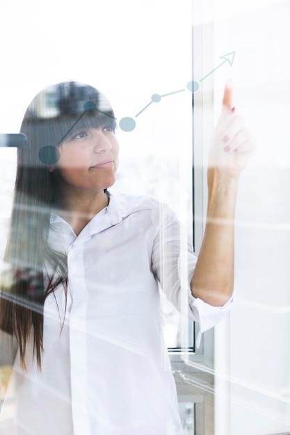 Jonge onderneemster die vinger richt op stijgende grafiek op transparant glas Gratis Foto