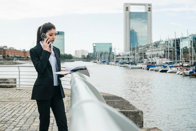 Jonge onderneemster die zich dichtbij de haven bevindt Gratis Foto