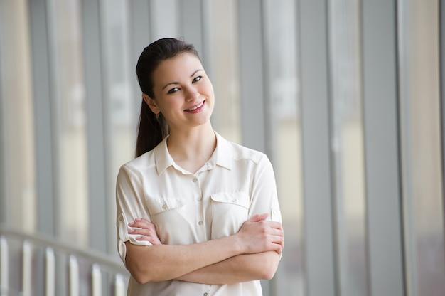 Jonge onderneemster die zich door venster met gekruiste wapens bevindt. Premium Foto