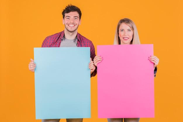 Jonge onderneemster en zakenman die blauw en roze aanplakbiljet houden tegen een oranje achtergrond Gratis Foto