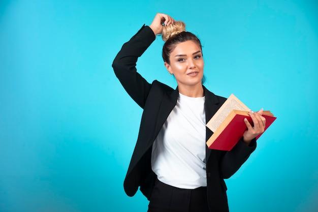 Jonge onderneemster in zwarte blazer die een taakboek houdt en haar broodje controleert. Gratis Foto