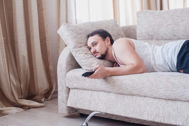 Jonge ongeschoren man die lui rust in een trainingspak Premium Foto