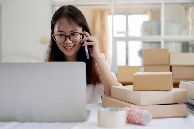 Jonge online verkoper die op telefoon spreekt om orde van klanten te ontvangen en te controleren Premium Foto