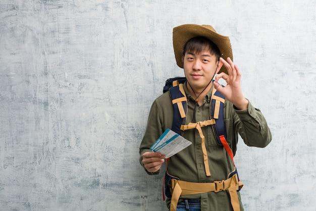 Jonge ontdekkingsreiziger chinese man met een vliegtickets vrolijk en vol vertrouwen doen ok gebaar Premium Foto