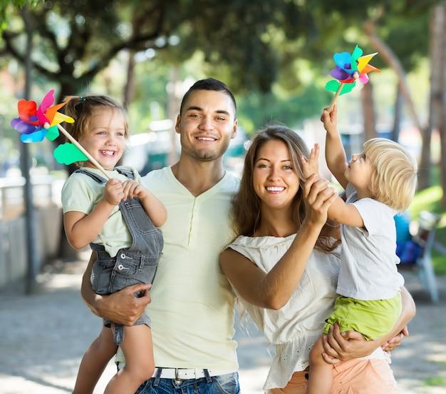 Jonge ouders met kinderen die windmolens spelen Gratis Foto