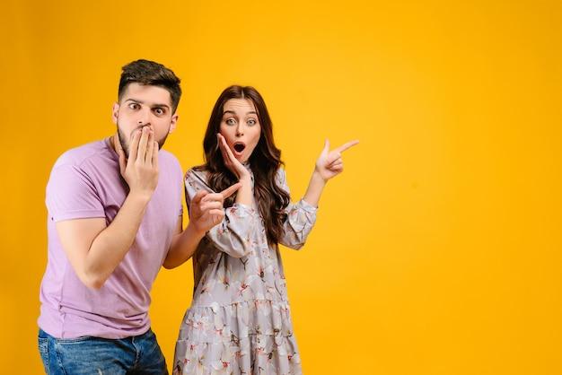 Jonge paar man en vrouw verrast wijzend op copyspace Premium Foto