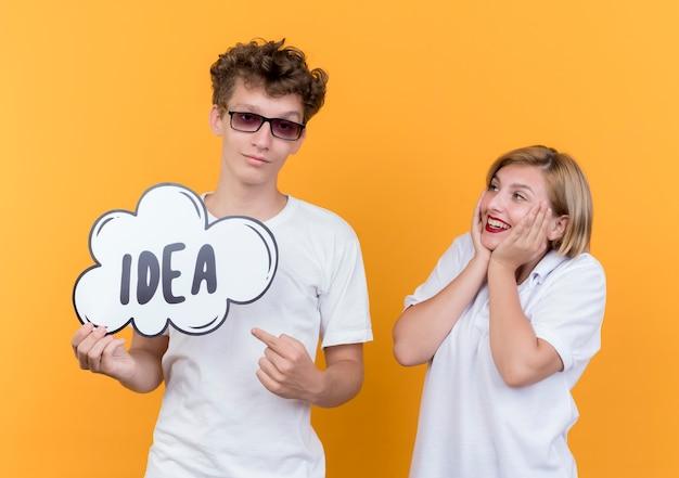 Jonge paarman en vrouw die zich samen glimlachend gelukkig en positief de bellenteken van de holdingstoespraak met woordidee over oranje muur bevinden Gratis Foto