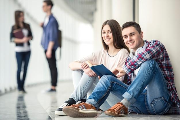 Jonge paarstudenten die in gang op universiteit zitten. Premium Foto