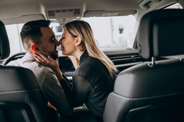 Jonge paarzitting in auto en het kussen Gratis Foto