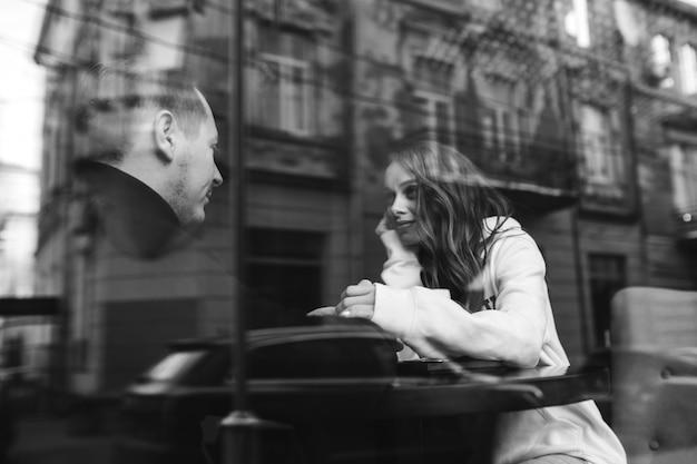 Jonge paarzitting in een koffie achter het venster Gratis Foto