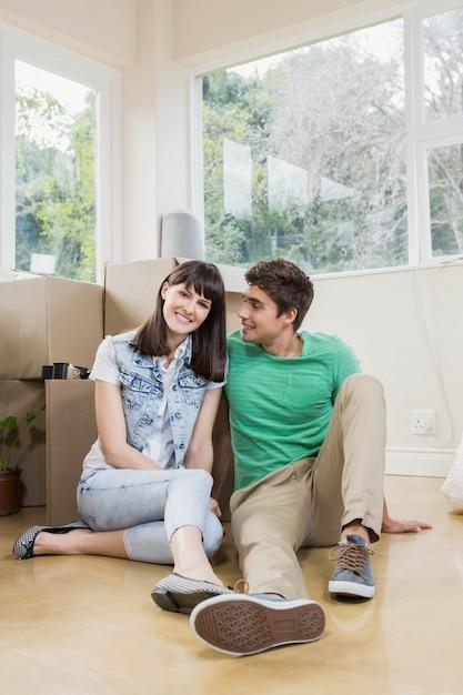Jonge paarzitting samen op de vloer en het glimlachen in hun nieuw huis Premium Foto