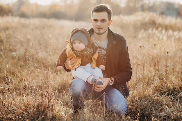 Jonge papa met het kindzitting van de zoonjongen in aard in de herfst Premium Foto