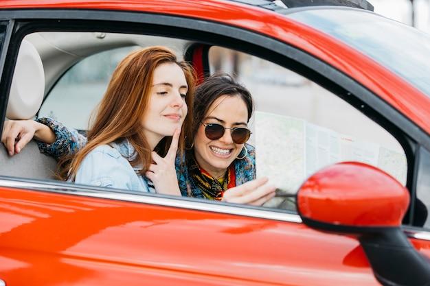 Jonge peinzende vrouw en het glimlachen dameperiezitting in auto en het bekijken kaart Gratis Foto