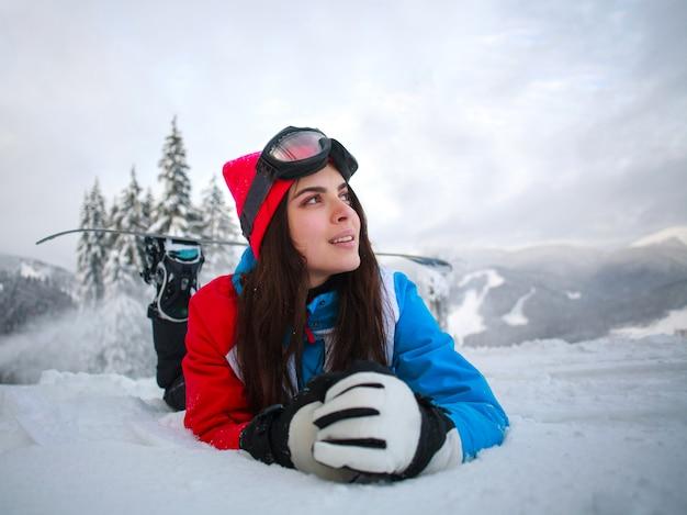 Jonge peinzende vrouw in de winter in sneeuwbos bovenop bergen Premium Foto