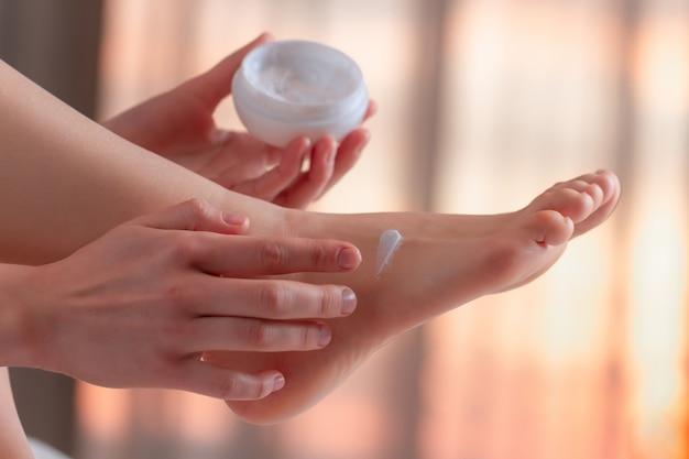 Jonge persoon die om haar voeten geeft en hydraterende, hydraterende crème aanbrengt. voet- en huidverzorging. Premium Foto